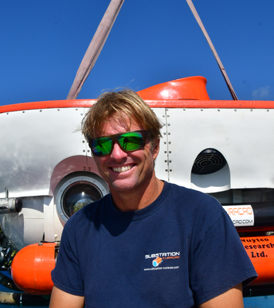 Bruce Brandt operational manager at substation Curaçao and a pilot is smiling towards the camera in front of the curasub.