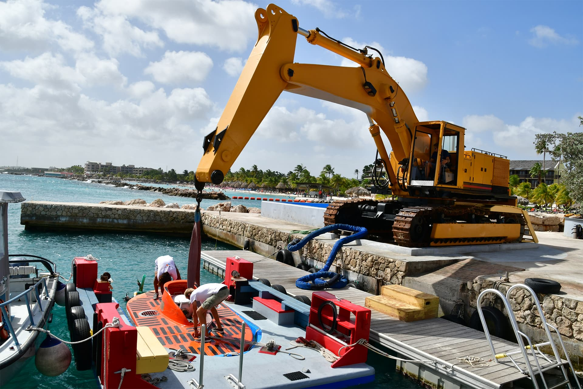 Crane keeps submarine in the water while workers prepare it to discover the unknown depths of Curaçao.