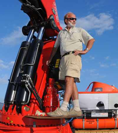 Adriaan 'Dutch' Schrier founder, developer and co-owner of the Curaçao Sea Aquarium standing on a crane in front of submarine.