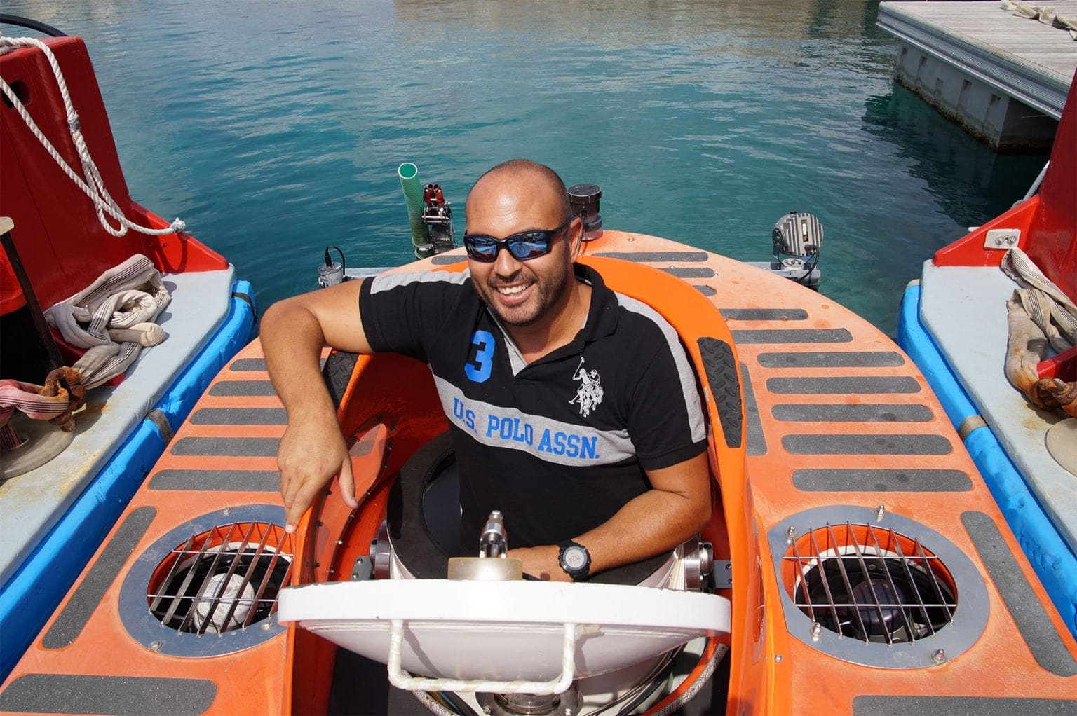 Happy tourist going in the submarine, looking at the camera, smiling exciting for the amazing experience in Curaçao.